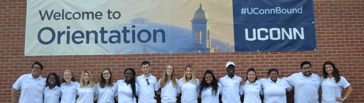 """2017 Summer Orientation staff stnds in front of a banner reading """"Welcome to Orientation"""""""