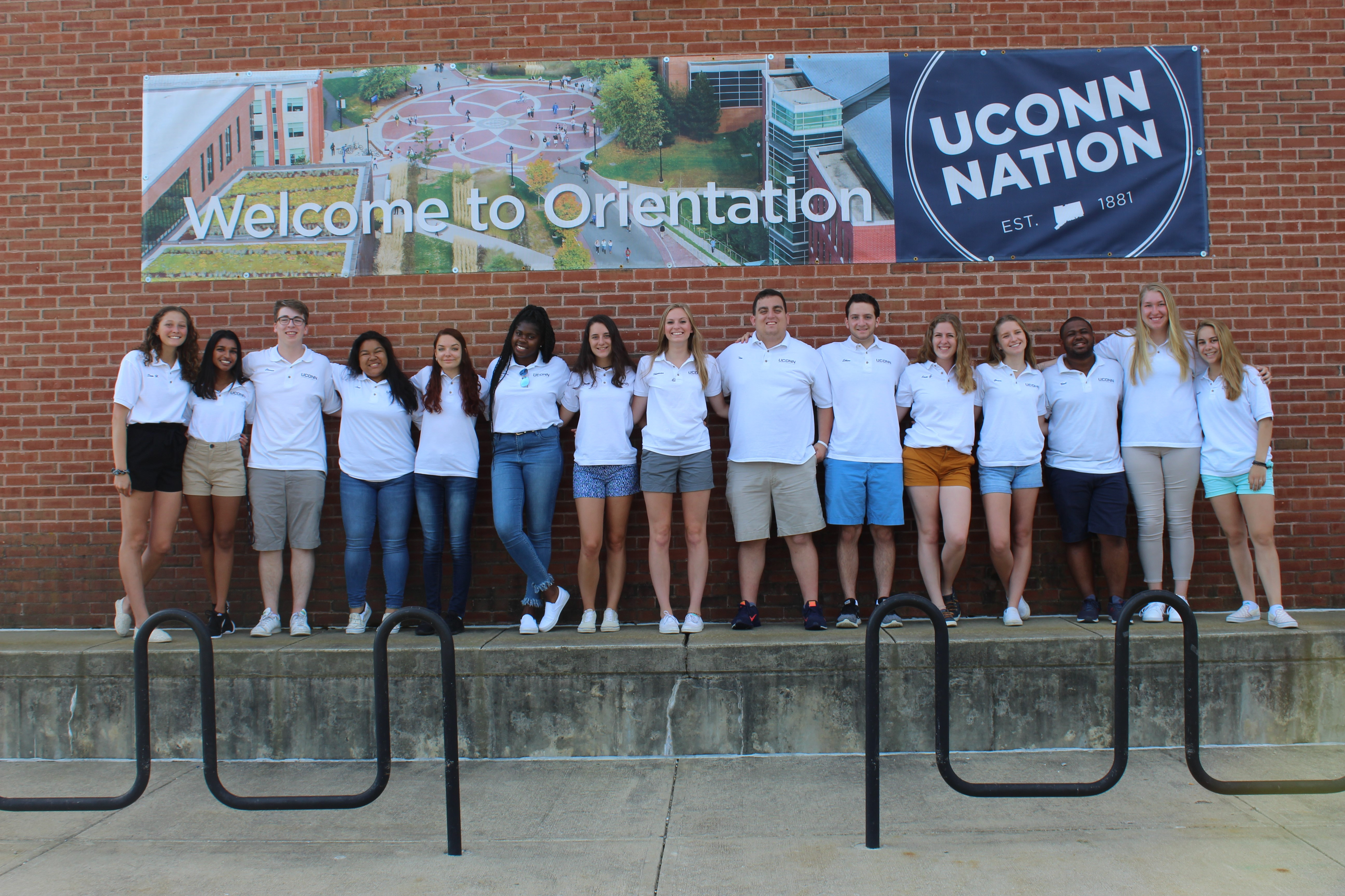 "2017 Summer Orientation staff stnds in front of a banner reading ""Welcome to Orientation"""